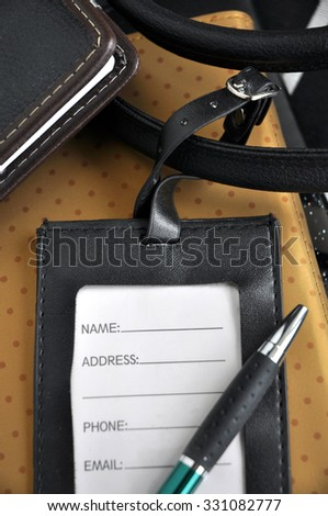 close up leather luggage tag with pen on notebook background