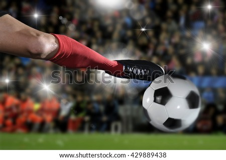 close up leg and soccer shoe of football player in action kicking ball wearing red jersey and sock playing on stadium with audience flashes  and lens flare on the background  - stock photo