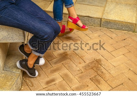 Close up leg  two Woman jeans and sneaker shoes sitting on stone chair outdoor