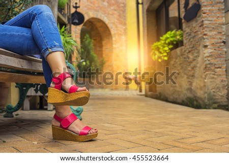 Close up leg Woman jeans and sneaker shoes sitting relaxing time on chair outdoor in old city - stock photo