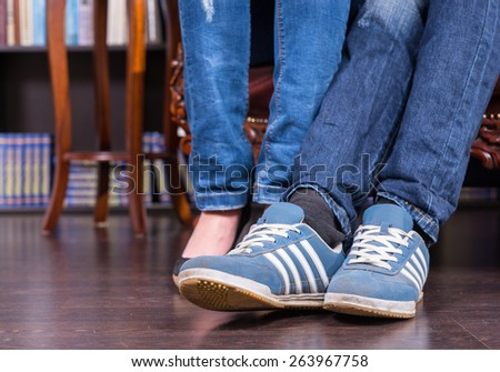 Close up Legs and Feet of a Couple Wearing Jeans and Shoes on the Wooden Floor. - stock photo