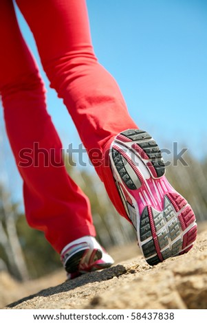 Close-up legs of a girl jogging on the wood - stock photo