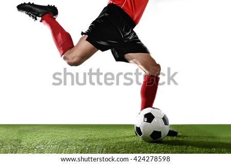 close up legs of football player in red socks and black shoes running and kicking the ball in free kick action playing isolated on white background - stock photo