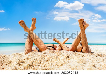 Close-up legs of several girls lying on sandy beach and tanning in the bright summer sun - stock photo
