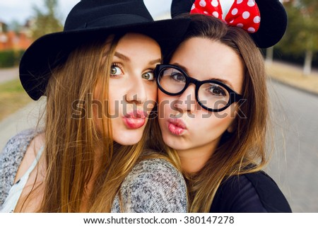Close up lifestyle cute portrait of two best friends   making self portrait , having fun, smiling. enjoying time together, Spring season mood. Natural make up. Blonde and brunette girls . Stylish hat. - stock photo