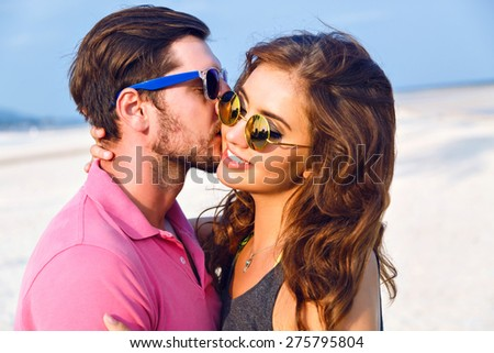 Close up lifestyle fashion portrait of attractive young hipster couple wearing sunglasses, handsome man kissing his brunette girlfriend to the cheek , happy day on the beach. - stock photo