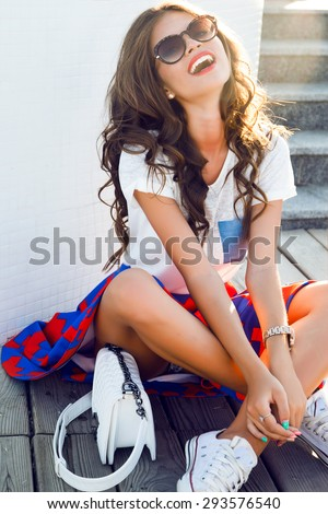 Close up lifestyle fashion portrait of cheerful brunette hipster girl going crazy making funny face and showing her bronze tongue.White urban wall background.sunset,summer accessory,laughing portrait - stock photo
