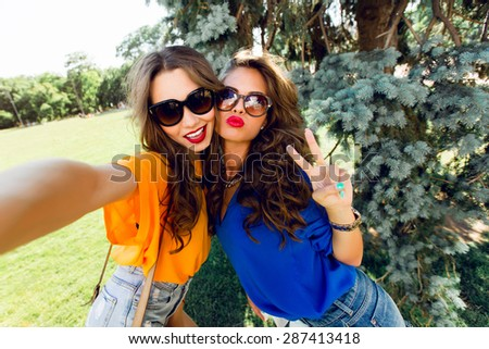 Close up lifestyle  image  of two best friends having fun and making self  portrait  together.    Bright colors.Wearing casual outfit. - stock photo