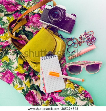 Close up lifestyle photo of hipster student accessories . Still life of random objects of modern girl / woman. Leather bag, camera, paper notepad, Aerial view. Sunny summer colors. Tropical print. - stock photo