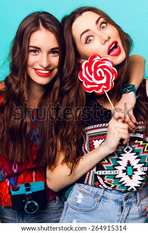 Close up  lifestyle portrait of two  attractive  cute   friends  in  colorful geometric  print    outfit .  Young model  holding a large pink lollipop delicious and laughing against blue wall. - stock photo
