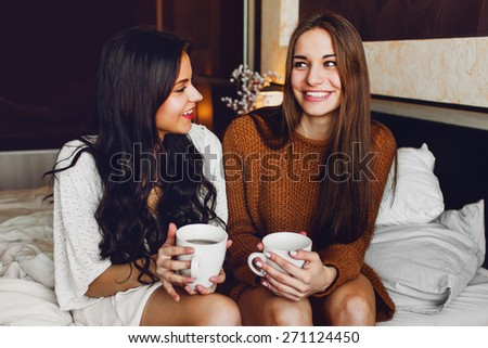 Close up lifestyle portrait of two best friends talking and laughing sitting on  bed at home. Enjoying sunny morning . - stock photo