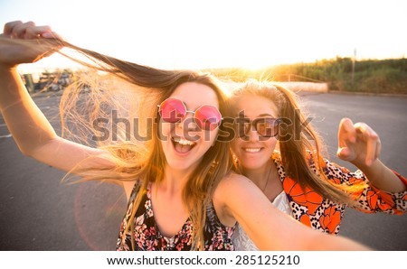 close-up lifestyle portrait of young best friends girls having fun at cool sunset.Travel concept,happy girls make picture together and having fun,laughing and make funny faces on camera,sunshine girls - stock photo