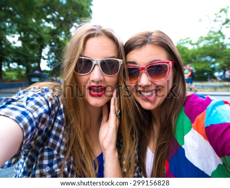 Close up lifestyle selfie portrait of pretty fresh young brunette and blonde best friends girls sisters making selfie,having fun, wearing sunglasses. Fresh make-up,teenage outfit,summer vacation. - stock photo