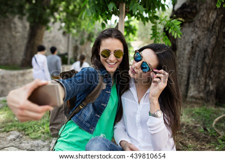 Close up lifestyle selfie portrait of two young positive woman having fun and making selfie. sisters, friends - stock photo