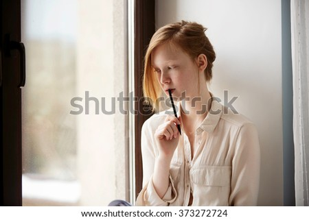 Close up lifestyle soft image of pretty young woman sitting on her window and making notes to her diary.  Fall season mood.