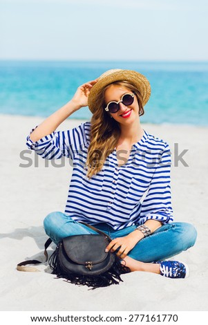 Close up  lifestyle  summer portrait of fresh young woman in cool sunglasses and straw hat sitting on the sunny tropical beach. Enjoying her vacation .