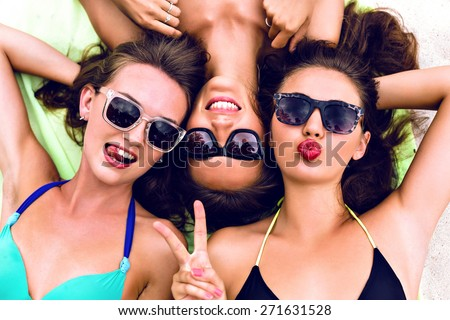Close up lifestyle summer portrait of thee girls friends relaxed and getting sunbathe, laying on the beach, wearing bright bikinis and stylish vintage sunglasses. Swing tongue, sending kiss. - stock photo