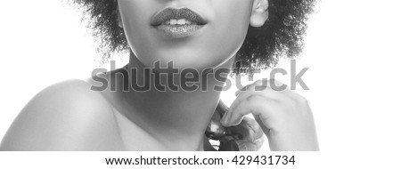 Close-up lips and shoulders of African woman with sparkle crimson lips, ethnic shawl and perfect skin. Isolated on white background. Black and white  - stock photo
