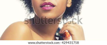 Close-up lips and shoulders of African woman with sparkle crimson lips, ethnic shawl and perfect skin. Isolated on white background. Toned - stock photo