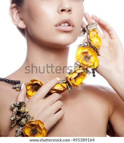 Close-up lips and shoulders of attractive caucasian young girl with natural make-up and yellow flowers necklace looking at camera. Studio shot Isolated on white background.
