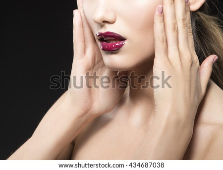 Close-up lips and shoulders of caucasian brunette woman wet wet red lipstick and arms touching face. Isolated on black background.