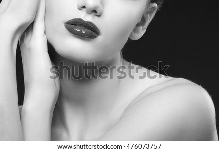 Close-up lips and shoulders of caucasian brunette woman wet wet red lipstick and arms touching face. Isolated on black background. Black and white