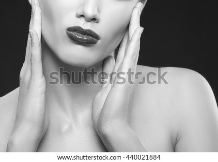 Close-up lips and shoulders of caucasian brunette woman wit negative emotions. Red glossy lipstick. Isolated on black background. Black and white