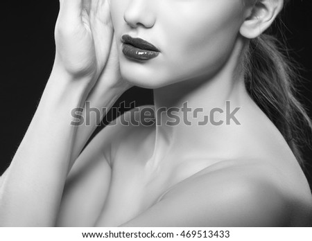 Close-up lips and shoulders of caucasian brunette woman with wet red lipstick and arms touching face. Isolated on black background. Black and white