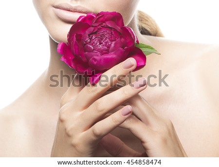 Close-up lips and shoulders of caucasian young brunette woman with peony flower in hand. Studio portrait. Isolated on white background.  - stock photo