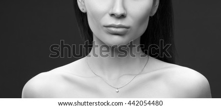 Close-up lips and shoulders of young brunette caucasian attractive sad woman with natural make-up. Studio portrait. Black and white - stock photo