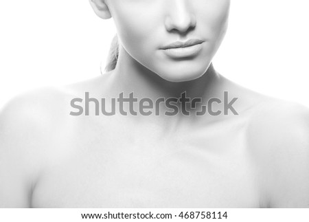 Close-up lips and shoulders of young caucasian brunette woman with natural lips, make-up, perfect skin and blue eyes isolated on white. Studio portrait. Black and white