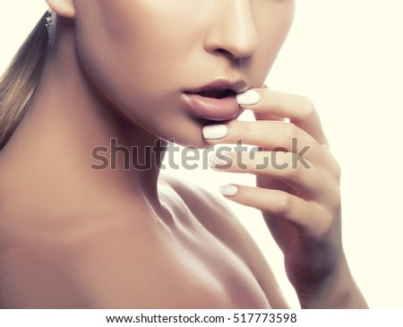 Close-up lips and shoulders of young caucasian girl with natural make-up, perfect skin and green eyes touching her lips isolated on white background. Studio portrait. Toned