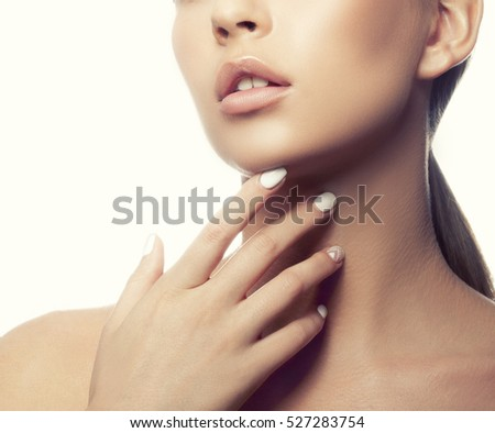Close-up lips and shoulders of young caucasian girl with natural make-up, perfect skin and green eyes touch her skin isolated on white background. Studio portrait. Toned