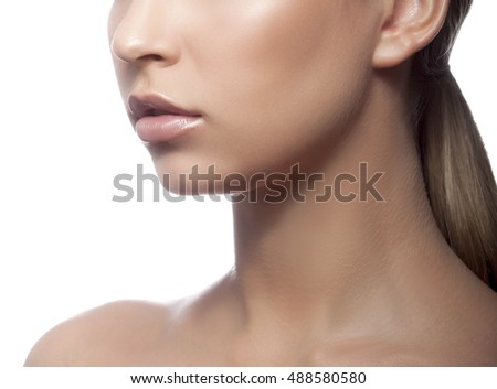 Close-up lips and shoulders of young caucasian woman with natural make-up, perfect skin and green eyes isolated on white. Studio portrait.