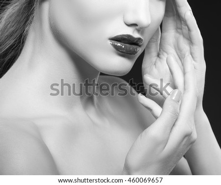 Close-up lips and shouldersof caucasian brunette woman with wet red lipstick and arms touching face. Isolated on black background. Black and white
