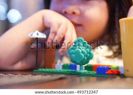 Close up Little asian girl playing with colorful toy blocks. Kids play with educational toys at kindergarten or day care. Preschool children build tower with plastic block. Toddler kid in nursery.