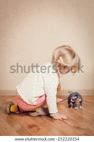 Close up Little Blond Female Kid Playing with Sphynx Kitten on the Floor at Home. - stock photo