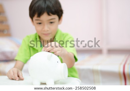 Close up Little boy saving money in piggy bank focus on piggy bank - stock photo