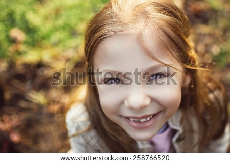 Close-up little girl's face with a smile and beautiful blue eyes looking at the camera. Photographed from above - stock photo