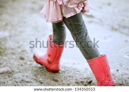 Close up little girl walking outdoors with red boots