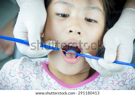 Close up little girl with Dentist examining a patient's teeth in the dentist