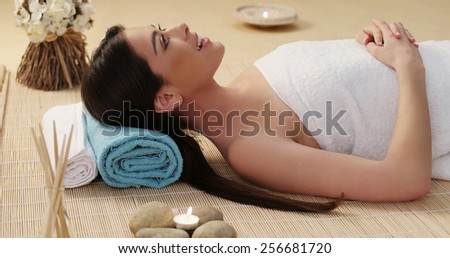Close up Long Hair Young Woman Lying Down in a Spa with White Towel Cover on her Body. - stock photo