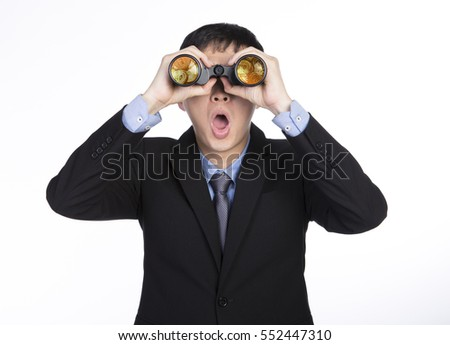 Close up look at asian businessman seeing through binoculars with shocked face in black suit, gold coins on the lens