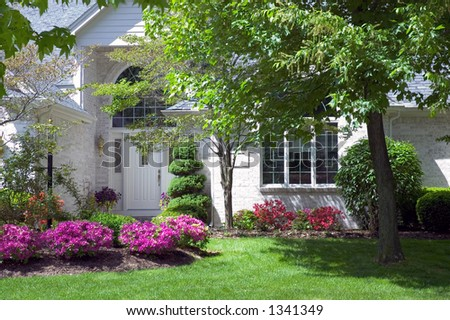 Close-up look at the main entrance to a new home. Beautiful blooming flowers to go with a beautiful new house. Just one of many new home photos in my gallery. - stock photo