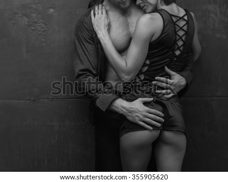 Close up lover couple. Passionate kissing, hugs. Man and woman standing on a stone wall background. Love relationship in a pair. Images of the novel about love. Woman dreams. Man instinct. Lose story. - stock photo