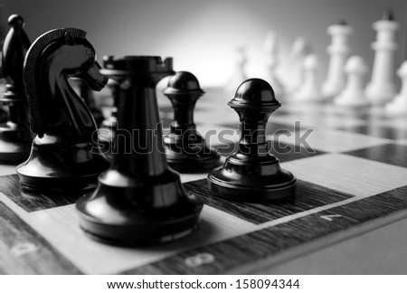 Close up low angle corner view of chess pieces lined up on a chess board ready for a game with focus to a black pawn with a castle and knight in the foreground - stock photo