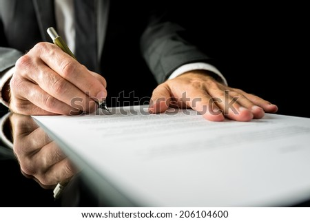 Close up low angle of the hands of a businessman in a suit signing a paper document with a fountain pen on a reflective desk top.