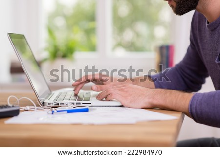 Close up low angle view of a man working from home on a laptop computer sitting at a desk surfing the internet - stock photo