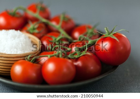 Close up low angle view of a plate of fresh ripe red cherry tomatoes on the vine with a small bowl of coarse sea salt ready to be used as ingredients in cooking - stock photo
