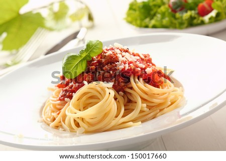 Close up low angle view of a plate of twirled spaghetti topped with delicious bolognaise sauce and basil - stock photo